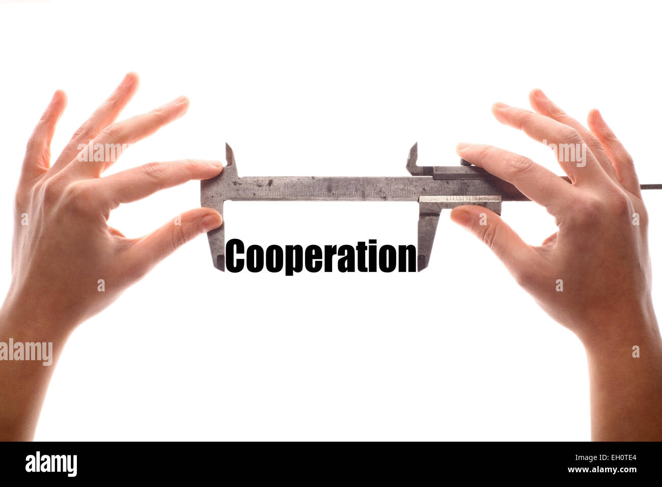 "Color horizontal shot of two hands holding a caliper and measuring the word ""cooperation"". Stock Photo"