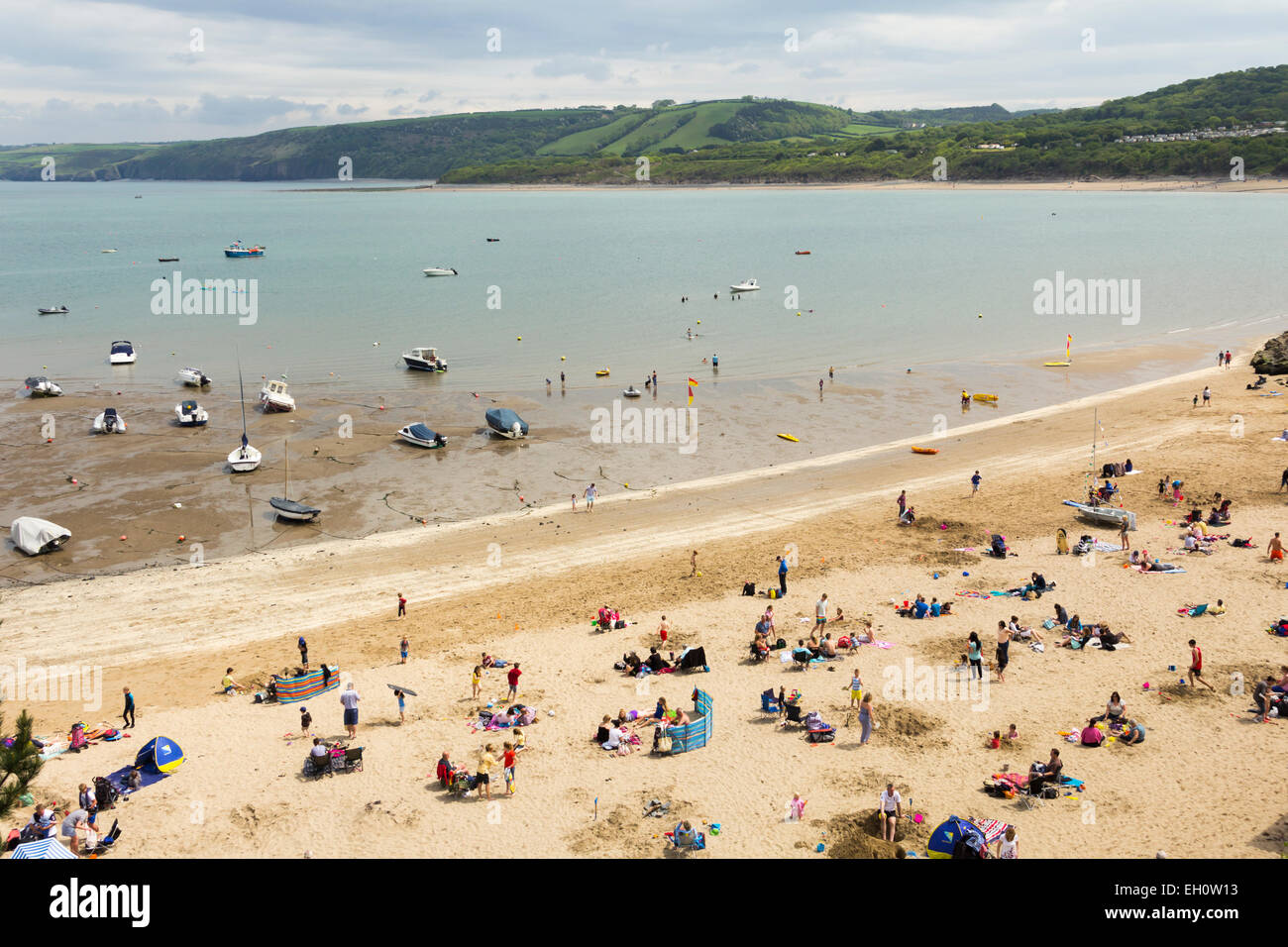 Holidaymakers on the beach near the harbour, New Quay, Ceredigion, Wales. - Stock Image