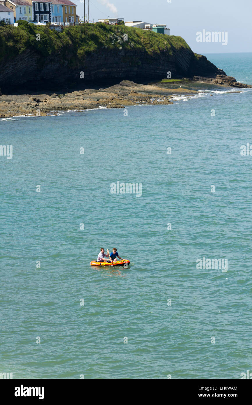 Small inflatable boat being paddled by two young men a little way off-shore of Traeth Y Dolau beach at New Quay, - Stock Image