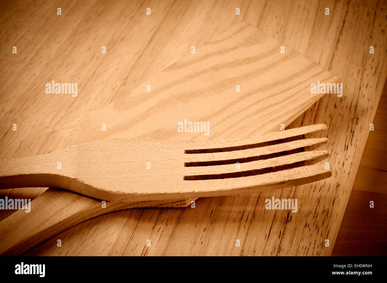 some wooden kitchen utensils on a wooden chopping board Stock Photo