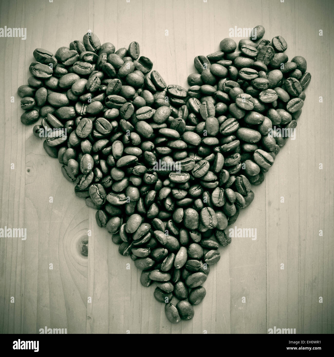 a pile of roasted coffee beans forming a heart, on a wooden table , in black and white - Stock Image