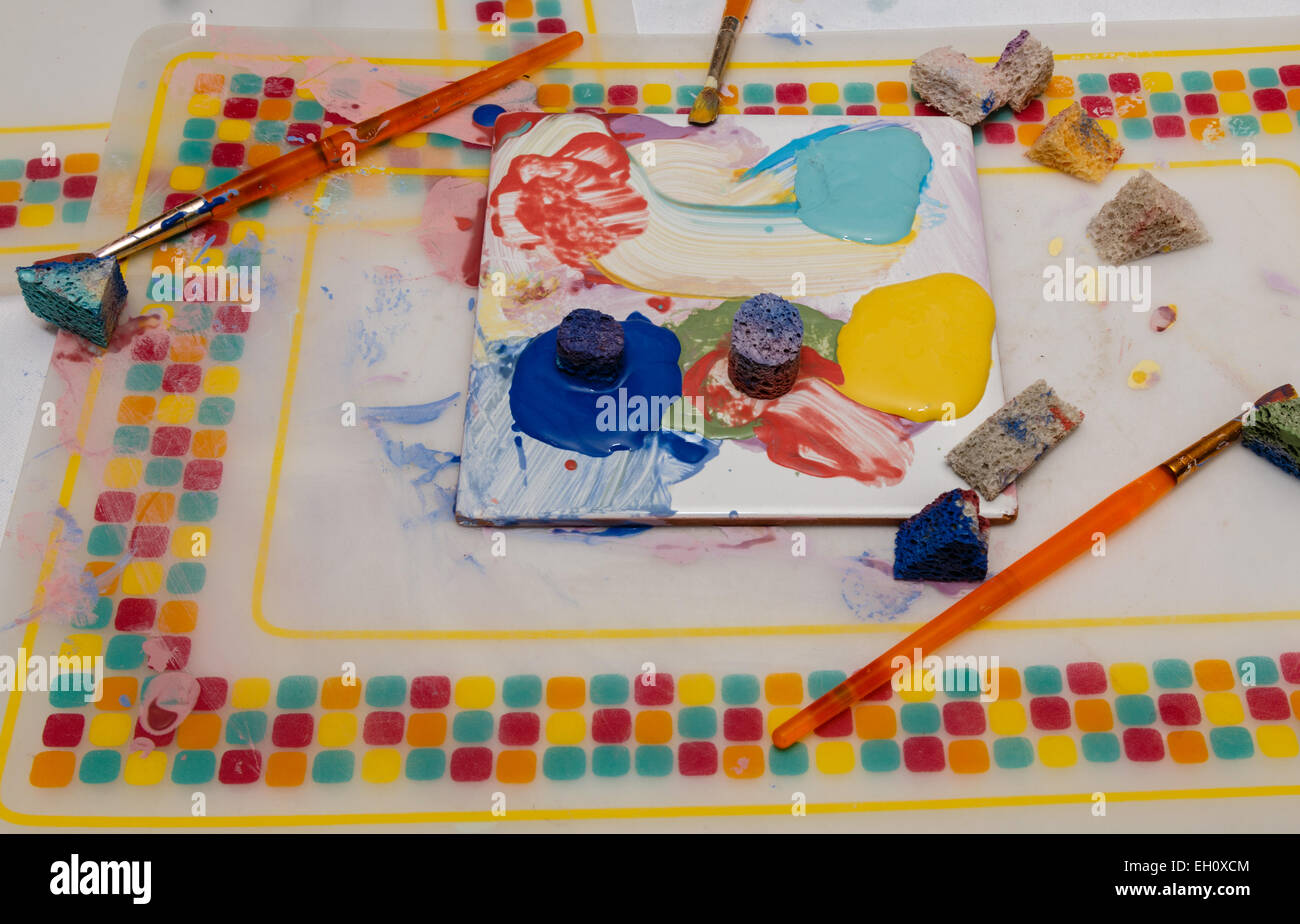 An artists mixing palette with ceramic paint sponges, brushes and paint for mixing - Stock Image