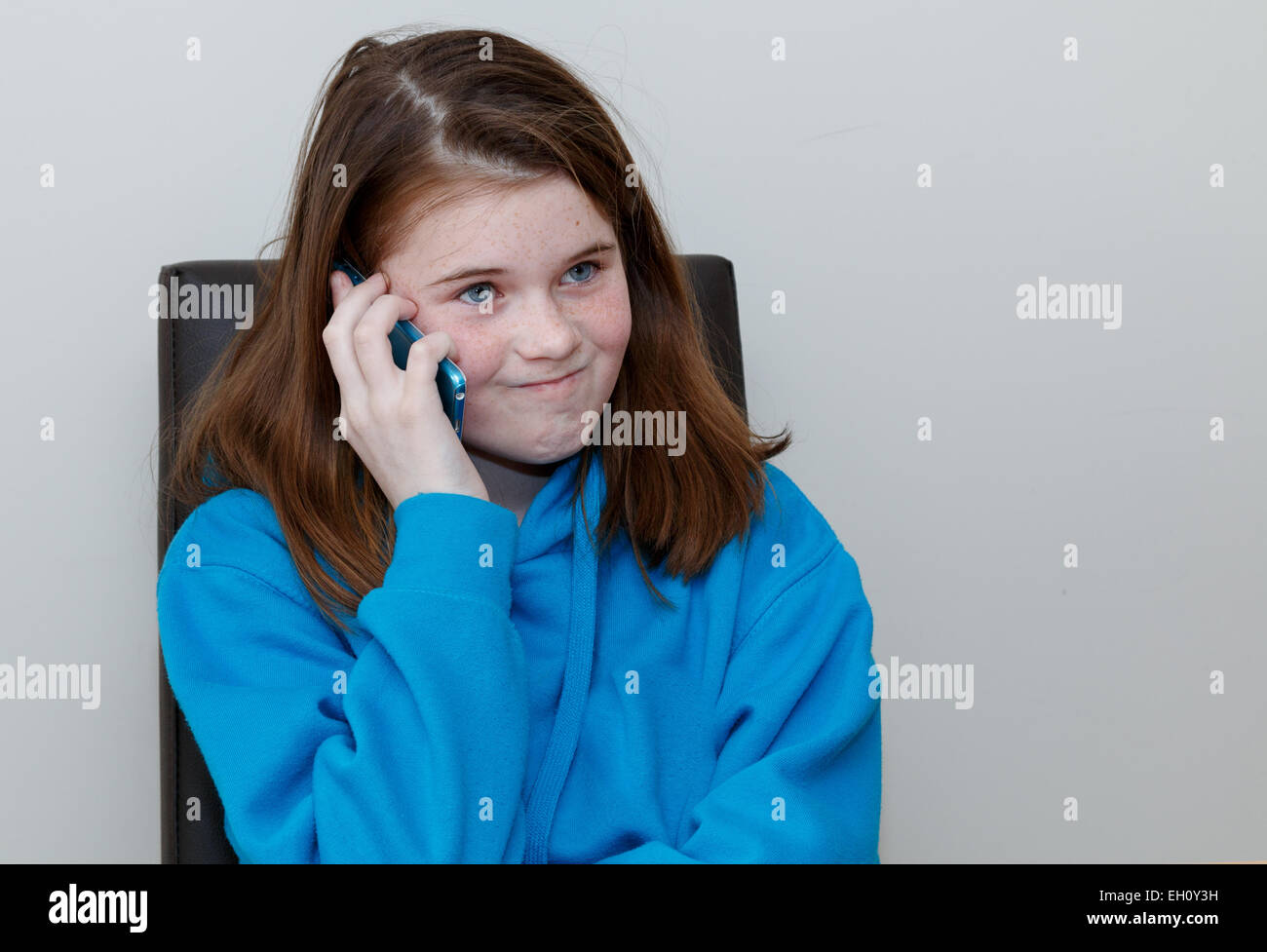 Young kid (girl 9-11 years) with red brown hair and freckles talking on a mobile phone looking frustrated and annoyed. - Stock Image