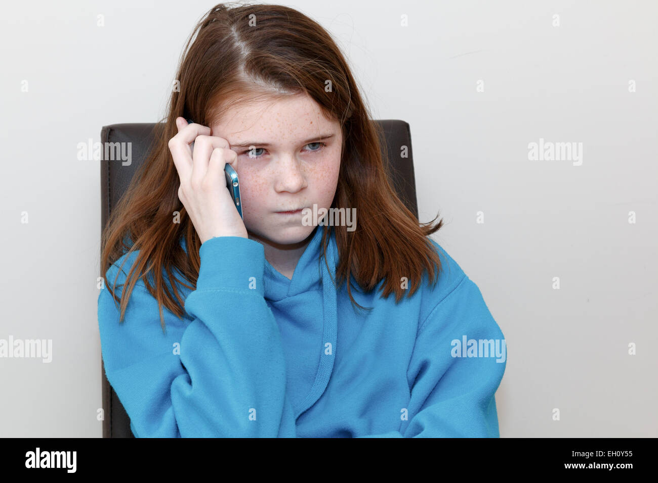 Girl (9-11 years) with red brown hair and freckles talking on a cell phone with a frown cross or angry expression. - Stock Image