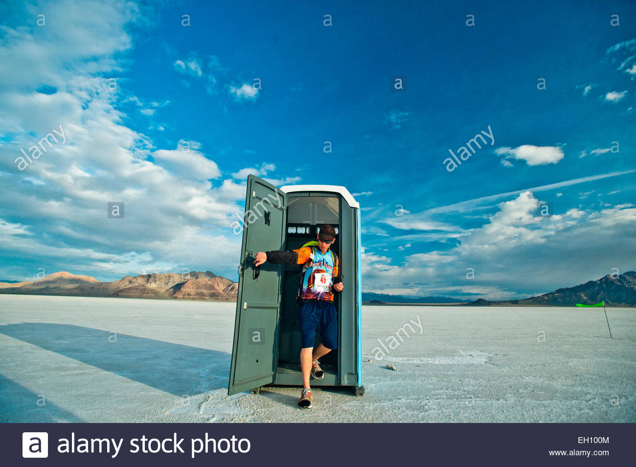 A competitor steps out of a porta-potty during the Salt Flats 100 in Bonneville, Utah. - Stock Image