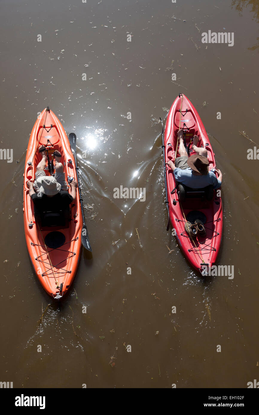 Two men pedel their small boats along the Oxford Canal, Oxfordshire, England - Stock Image