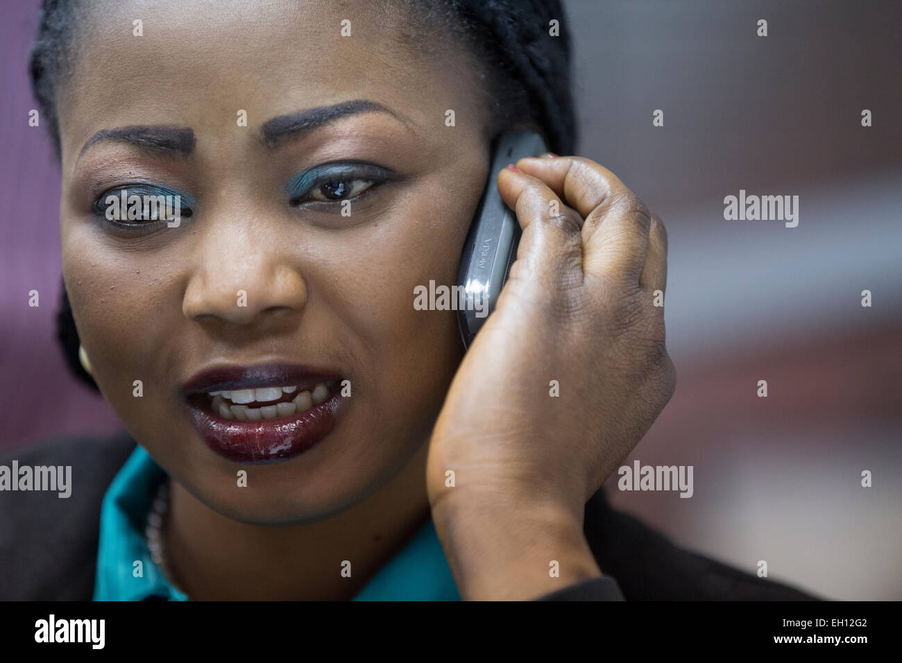Lagos, Nigeria; A young woman on her mobile phone in a city office. - Stock Image