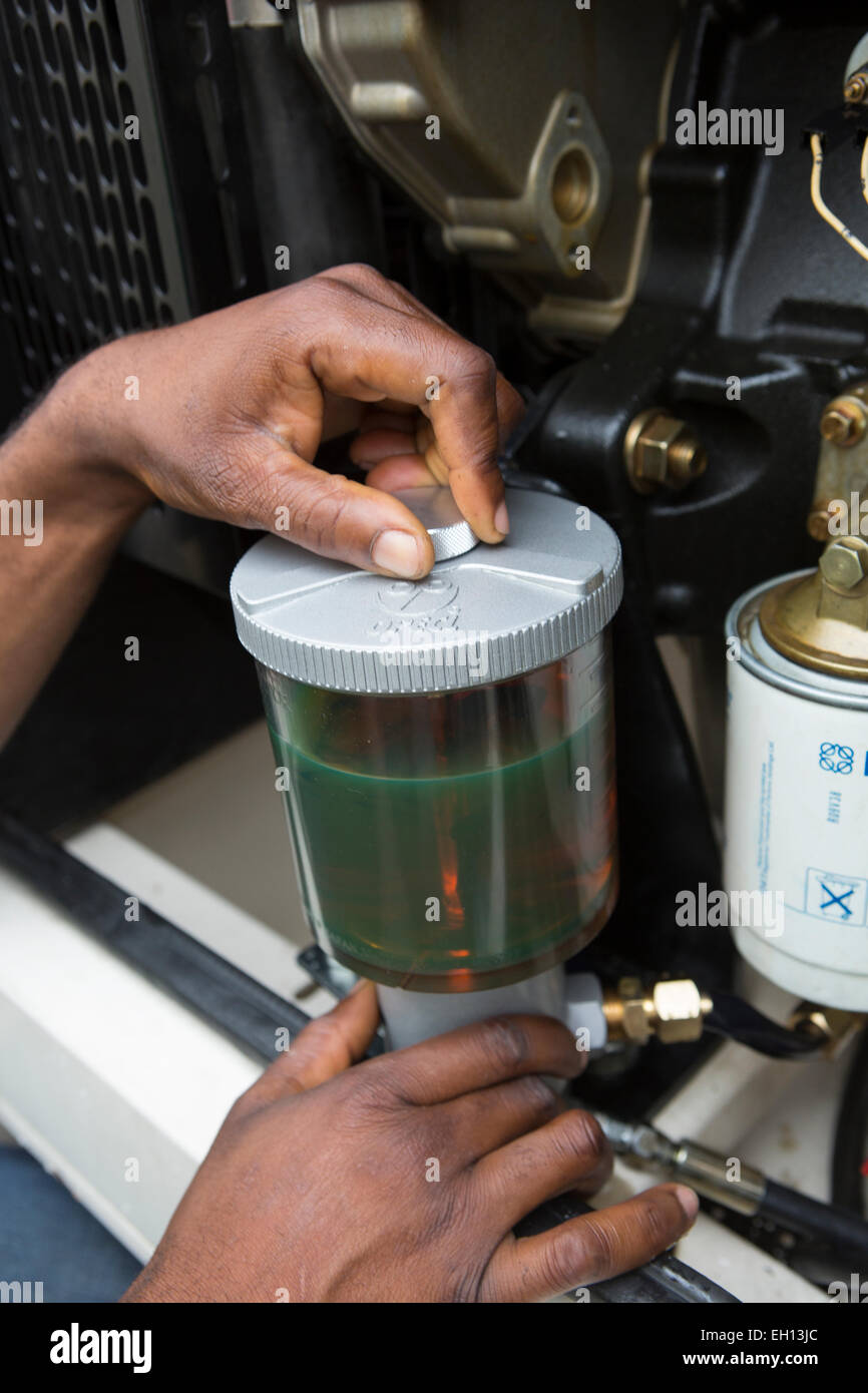 Lagos, Nigeria; changing an oil filter on a diesel electricity generator - Stock Image