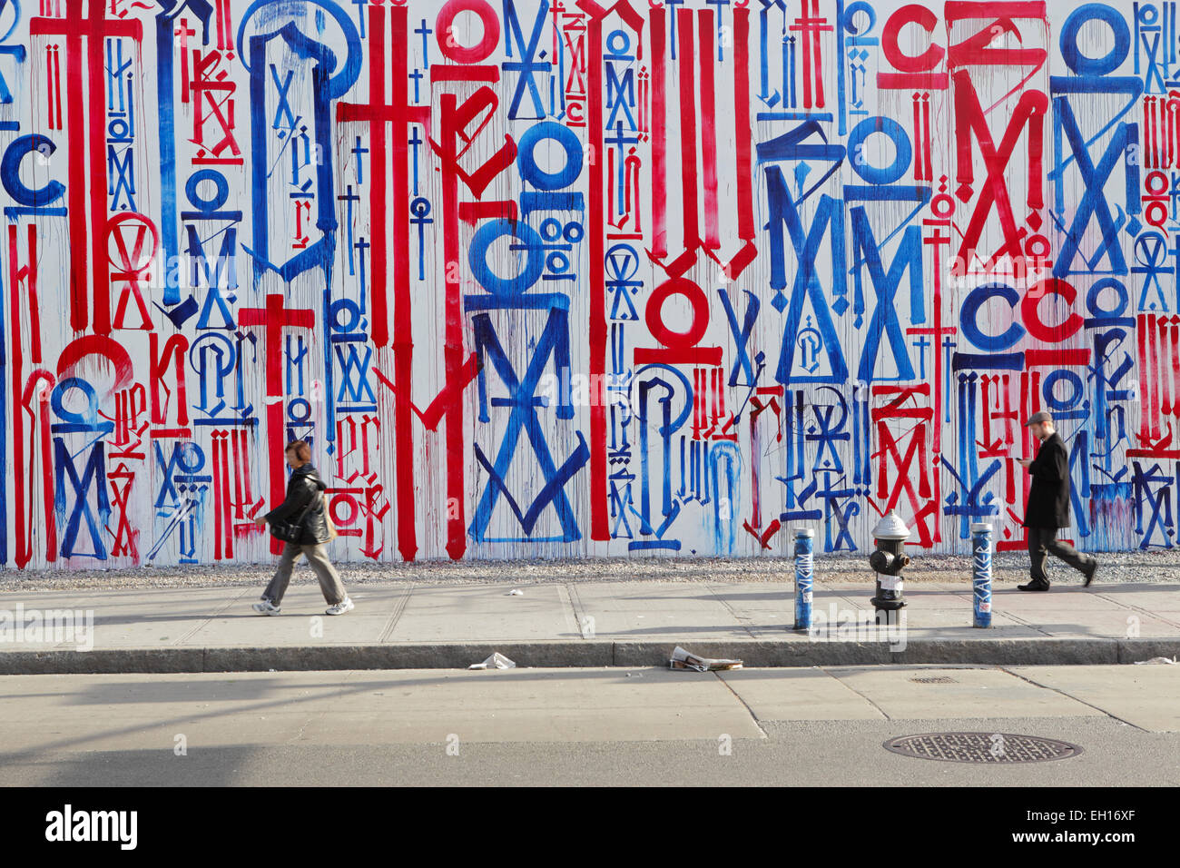 Local people walking to work past a colourful mural painted by RETNA