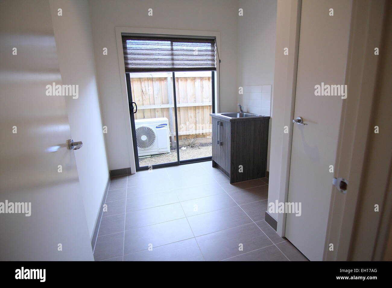 Modern laundry room with tile floor and glass door Stock Photo ...