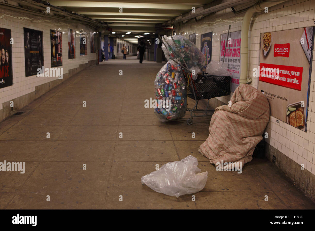 Can and bottle collector sleeps on East Broadway subway station in New York - Stock Image