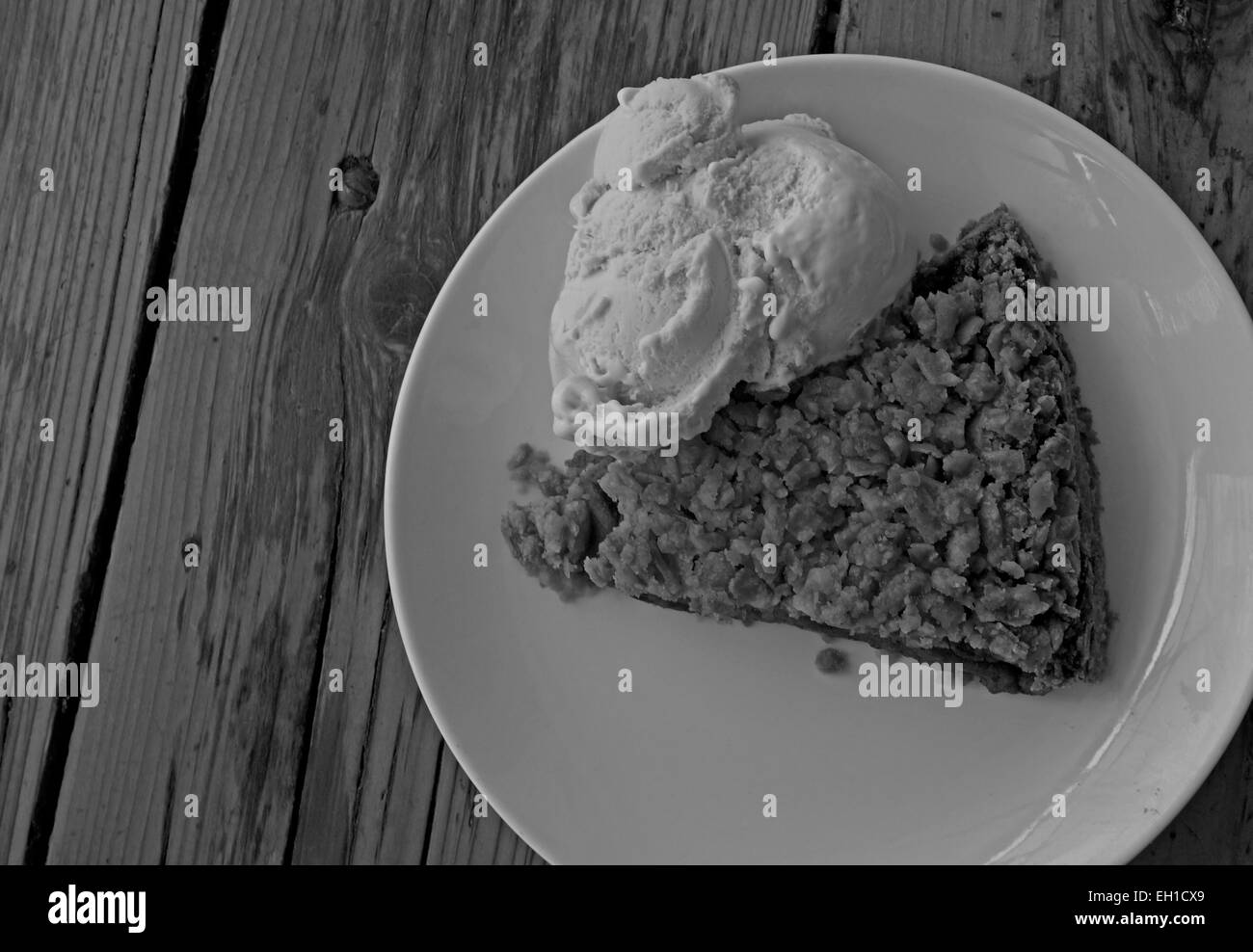 Black and white photograph of a piece of apple pie with ice cream on a plate. - Stock Image