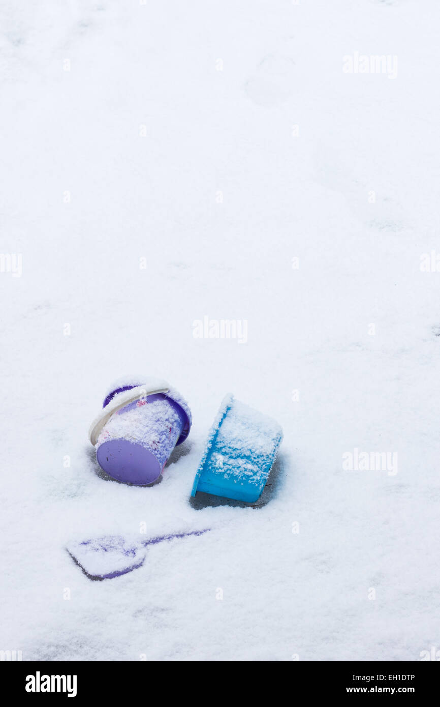 Children's toys left behind on a snowy ground, copy space. - Stock Image