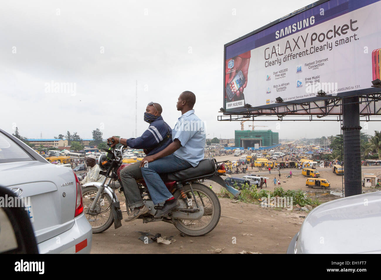 Lagos, Nigeria; People on a motorbike in heavy traffic. - Stock Image