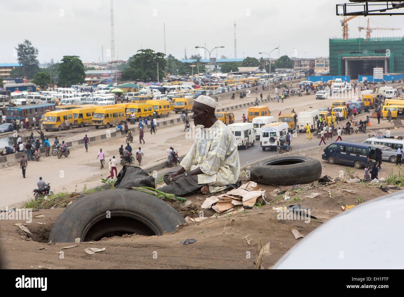 Lagos, Nigeria; On old man sits by the roadside overlooking a bus station in the capital. - Stock Image