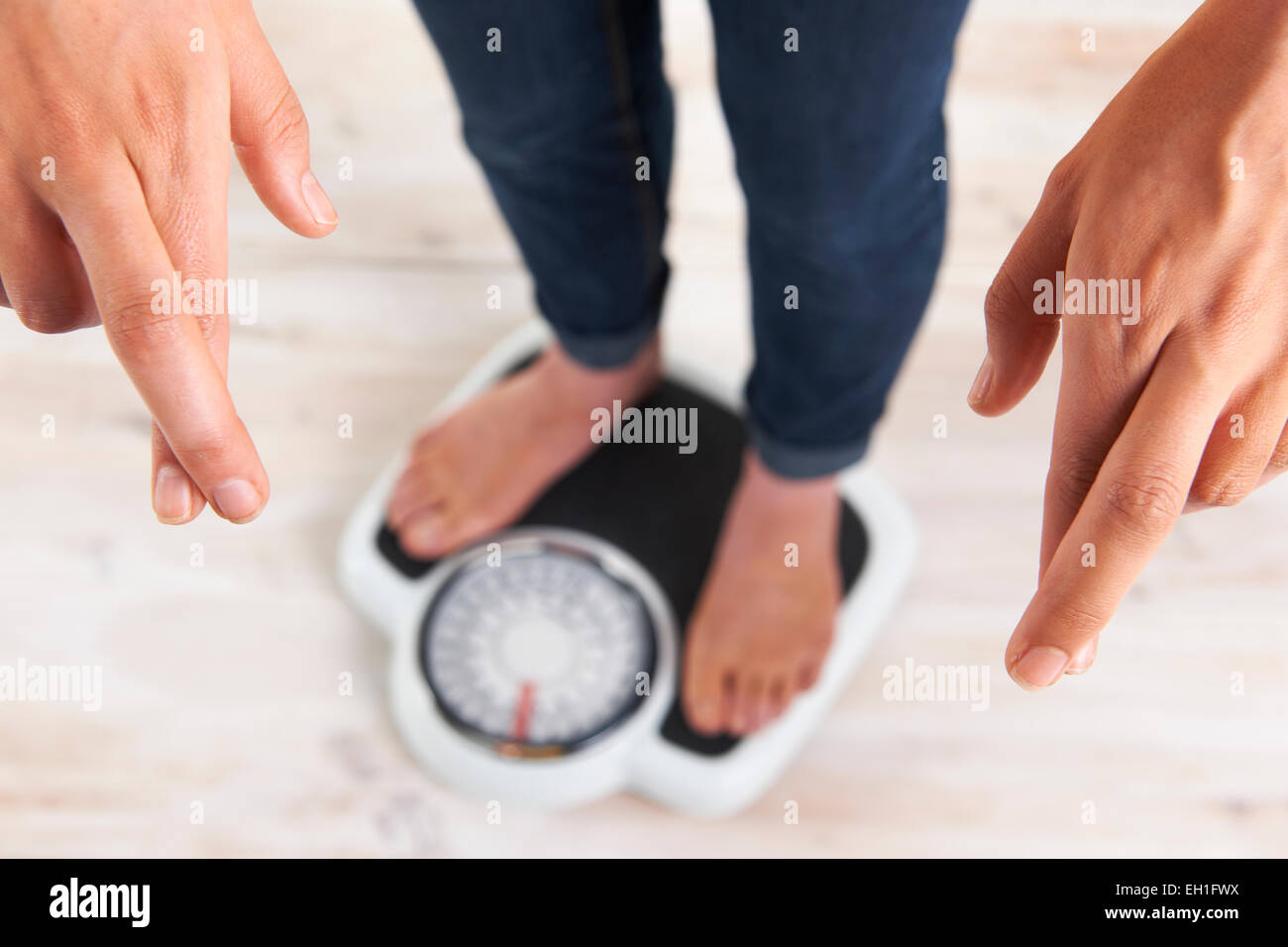 Woman Standing On Scales With Fingers Crossed - Stock Image