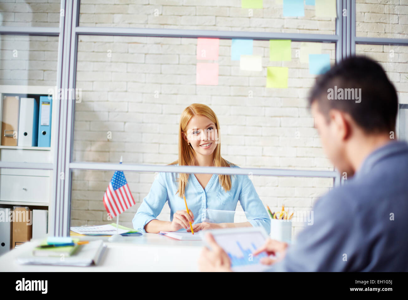Young businesswoman looking at co-worker at meeting in office - Stock Image