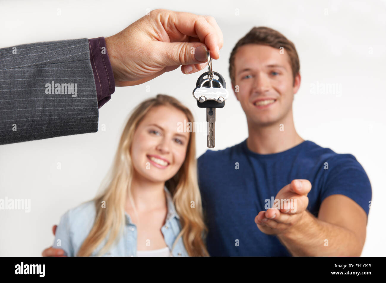 Dealer Handing Over Keys For New Car To Young Couple - Stock Image