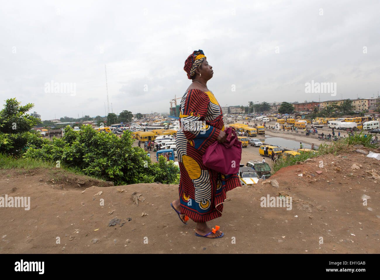 Lagos, Nigeria; A woman walks by the roadside overlooking a bus station in the capital. - Stock Image