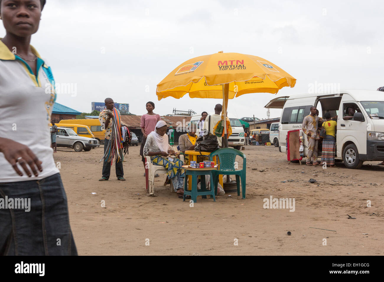 Lagos, Nigeria; People sit under an MTN umbrella in a carpark in th capital - Stock Image