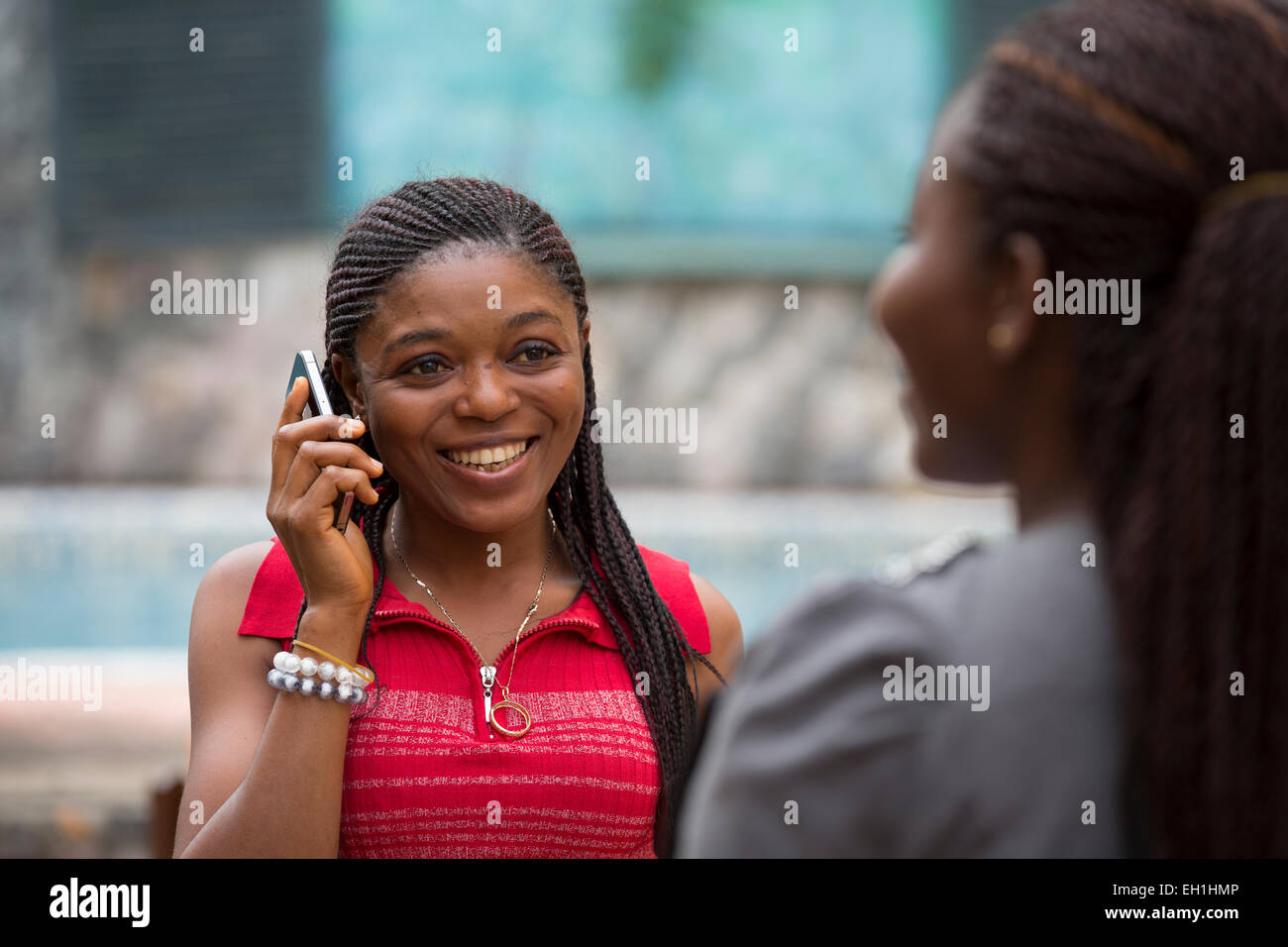 Lagos, Nigeria; A young woman on her mobile phone in a city street. - Stock Image