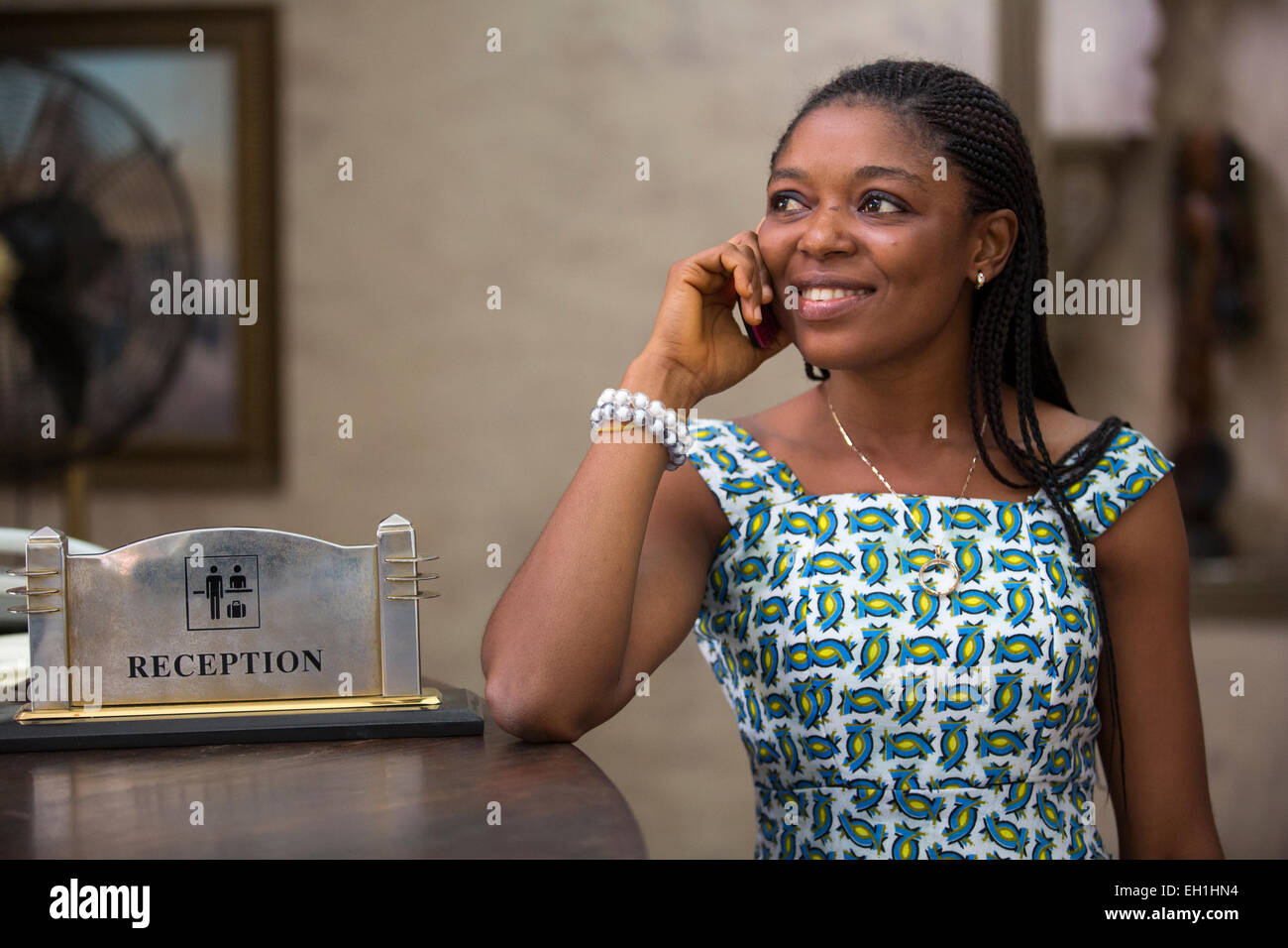 Lagos, Nigeria; A young woman on her mobile phone in a hotel lobby. - Stock Image