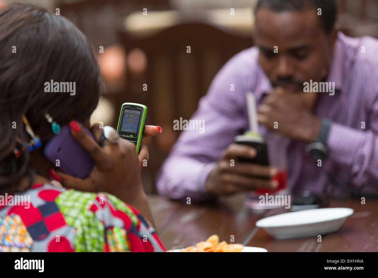 Lagos, Nigeria; A young woman on her mobile phone in an outdoor city restaurant. - Stock Image