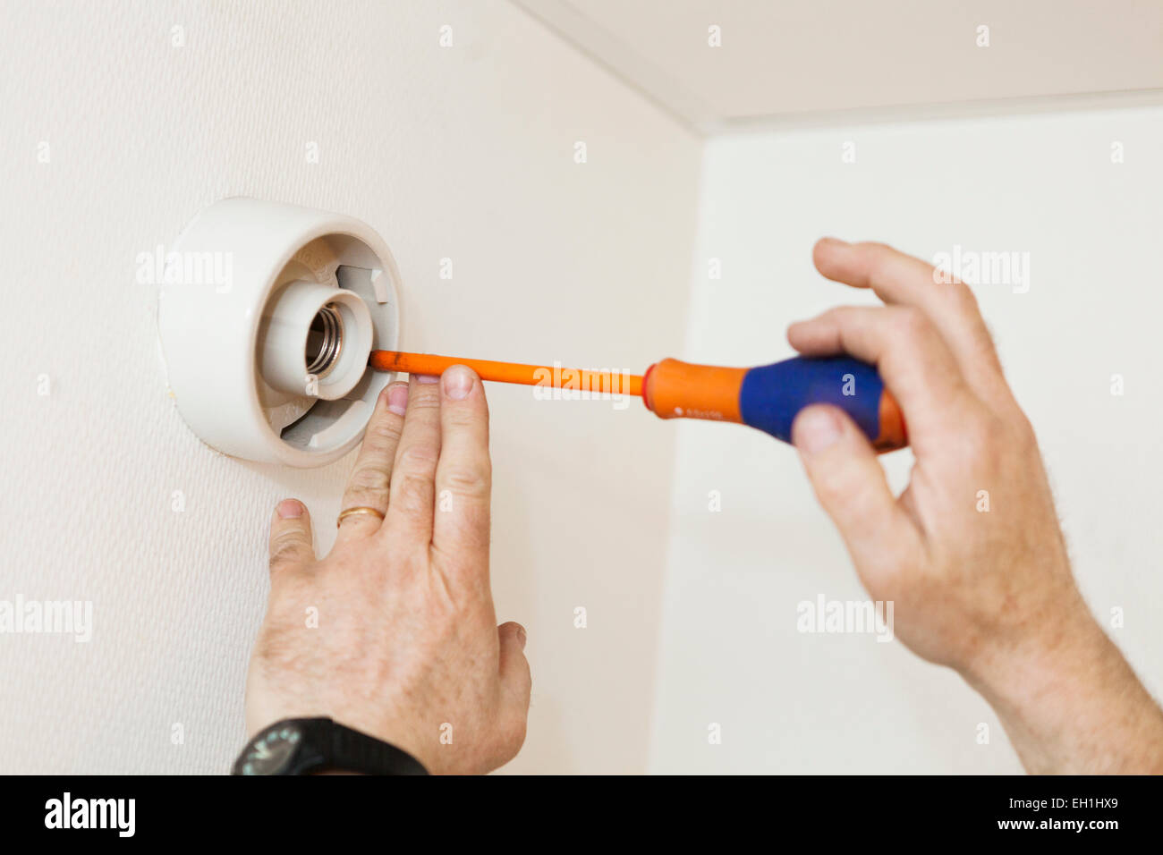 Cropped image of electrician's hands using screwdriver on bulb socket Stock Photo