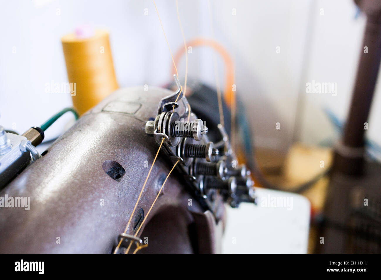 Close-up of sewing machine at jeans factory - Stock Image