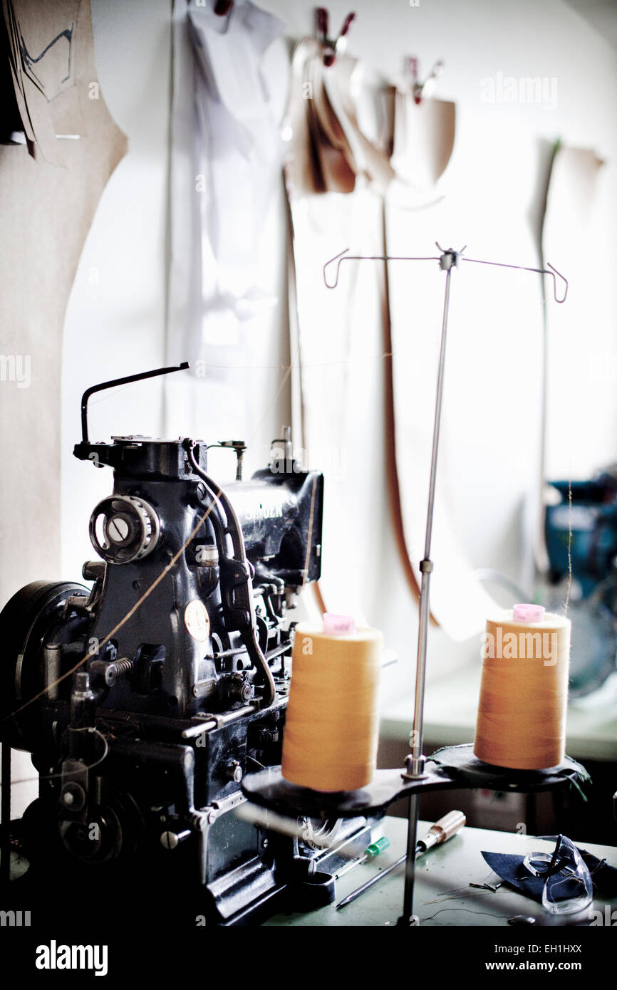 Spools and sewing machine at jeans factory - Stock Image