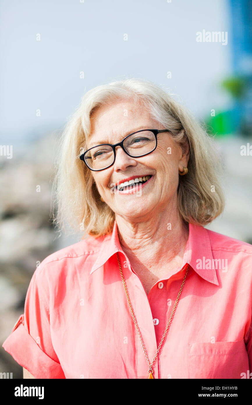 Smiling senior woman wearing glasses outdoors - Stock Image