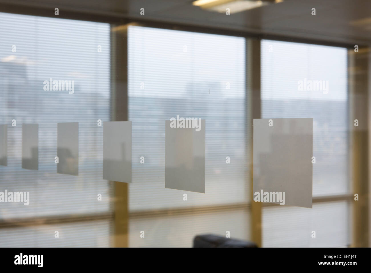 Glass wall on a Mmodern office interior with open plan desking - Stock Image