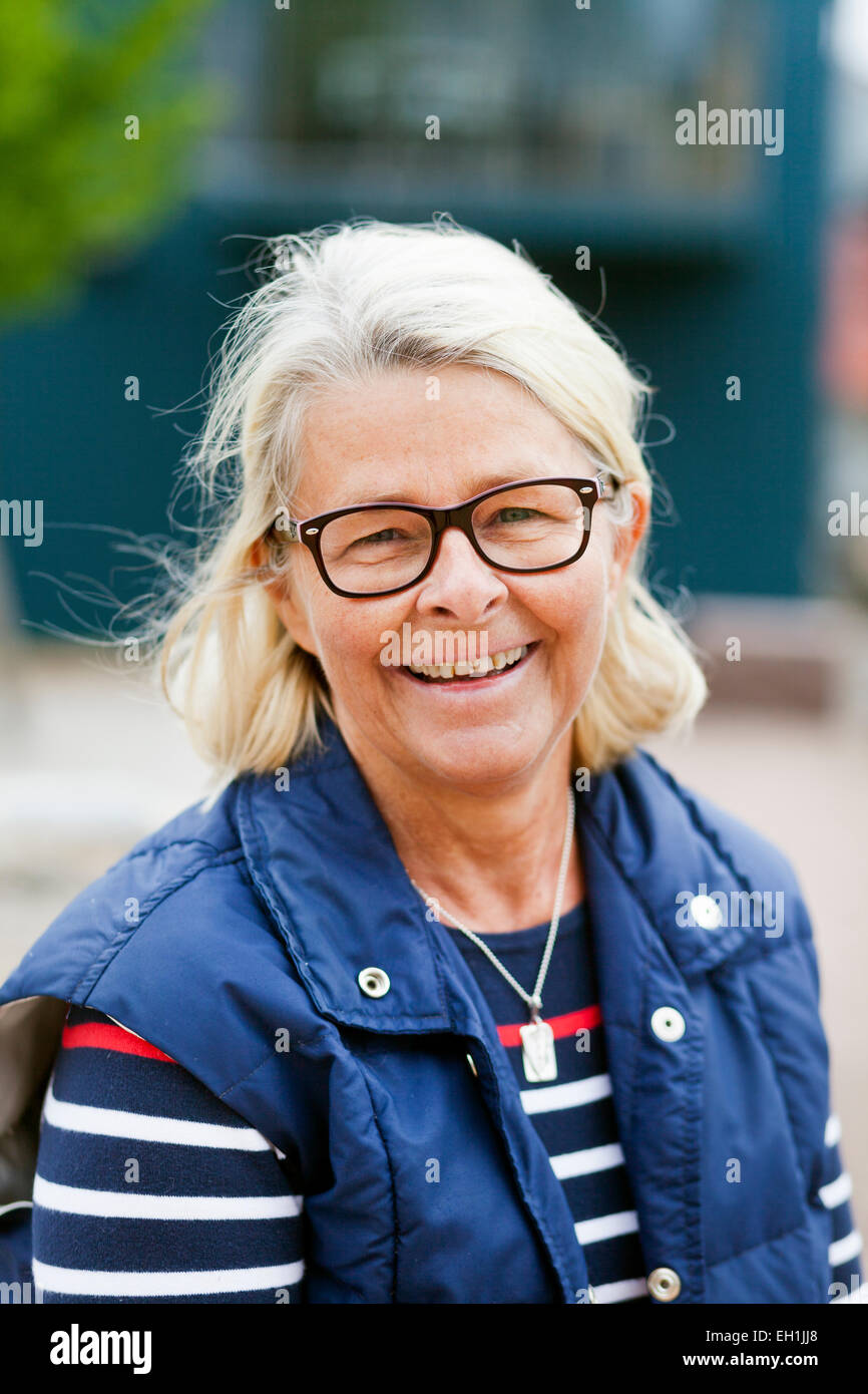 Portrait of smiling senior woman wearing glasses outdoors - Stock Image
