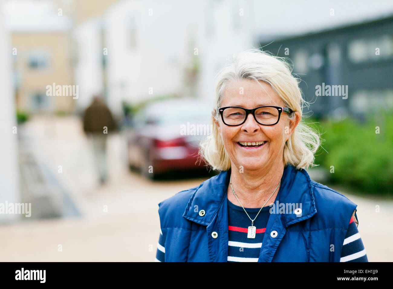Portrait of smiling senior woman wearing glasses on street - Stock Image
