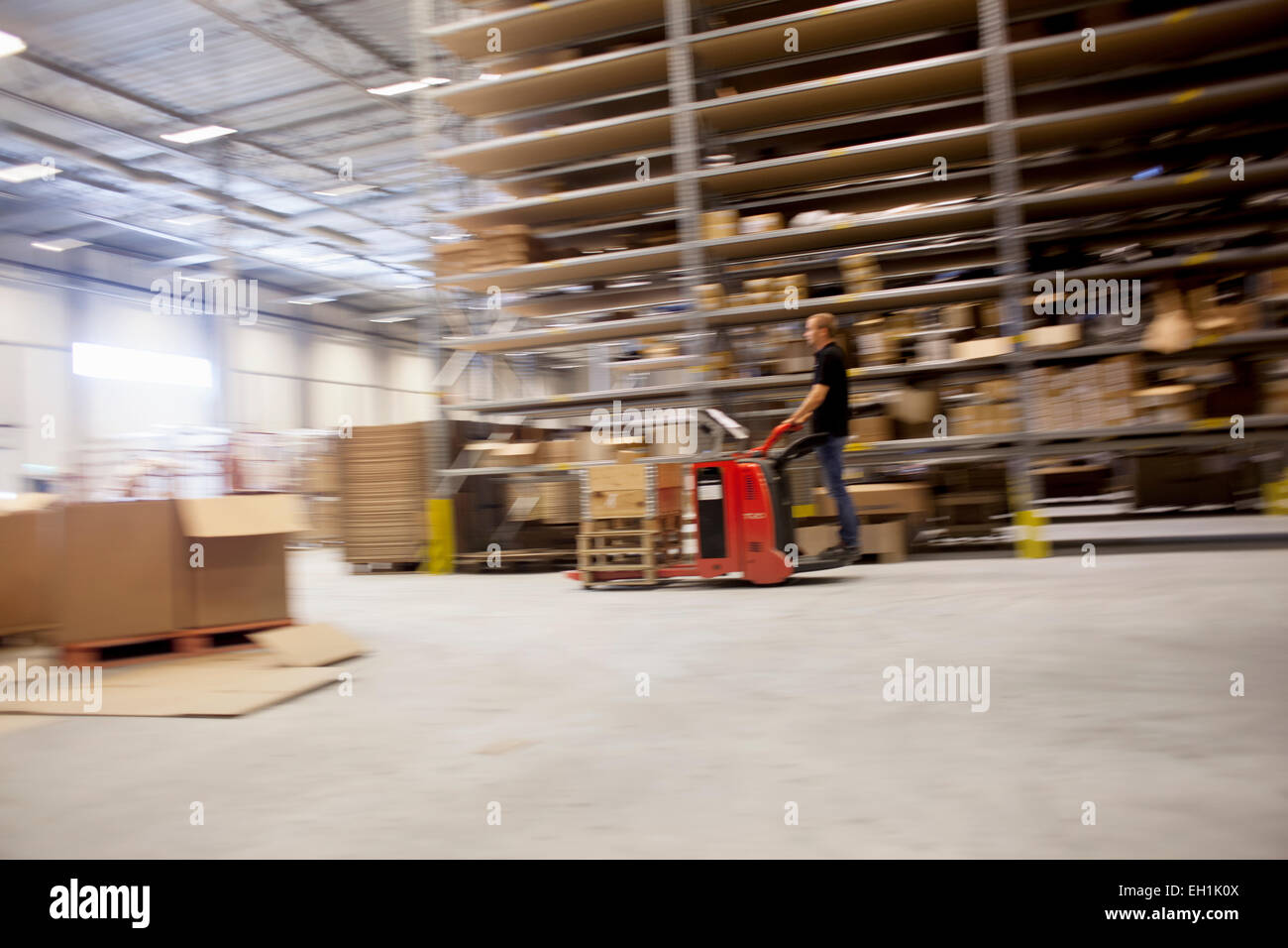 Man driving forklift truck in factory warehouse - Stock Image