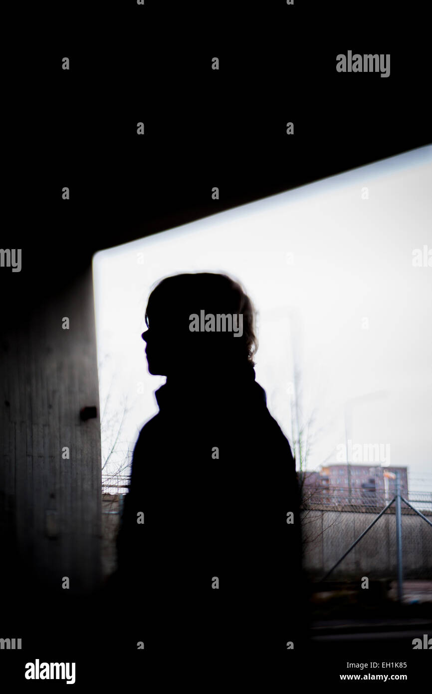 Silhouette person standing against window Stock Photo