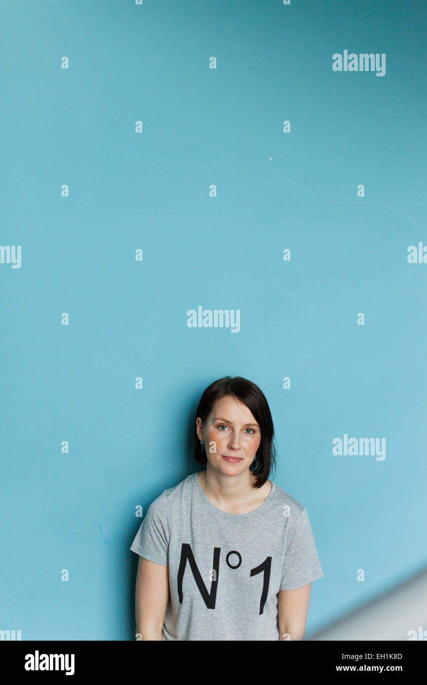 Portrait of happy woman standing against blue wall - Stock Image