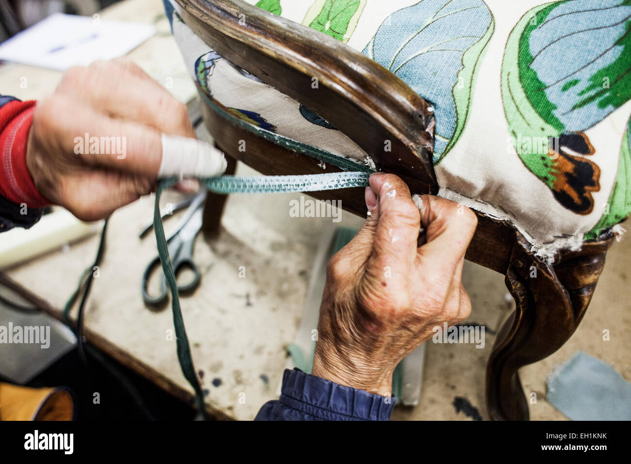 Cropped image of worker's hands making chair in workshop - Stock Image