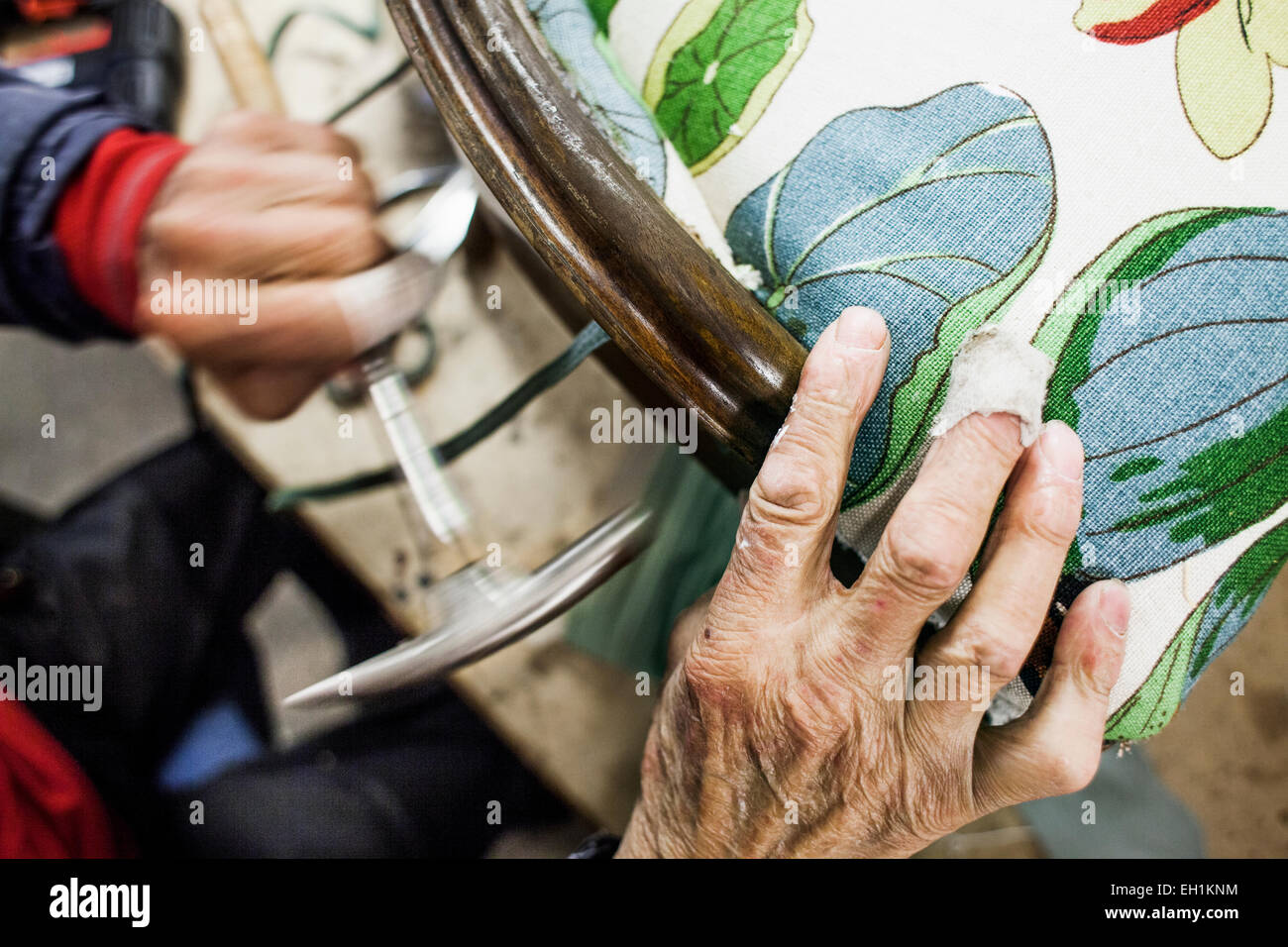 Cropped image of worker hammering chair in workshop - Stock Image