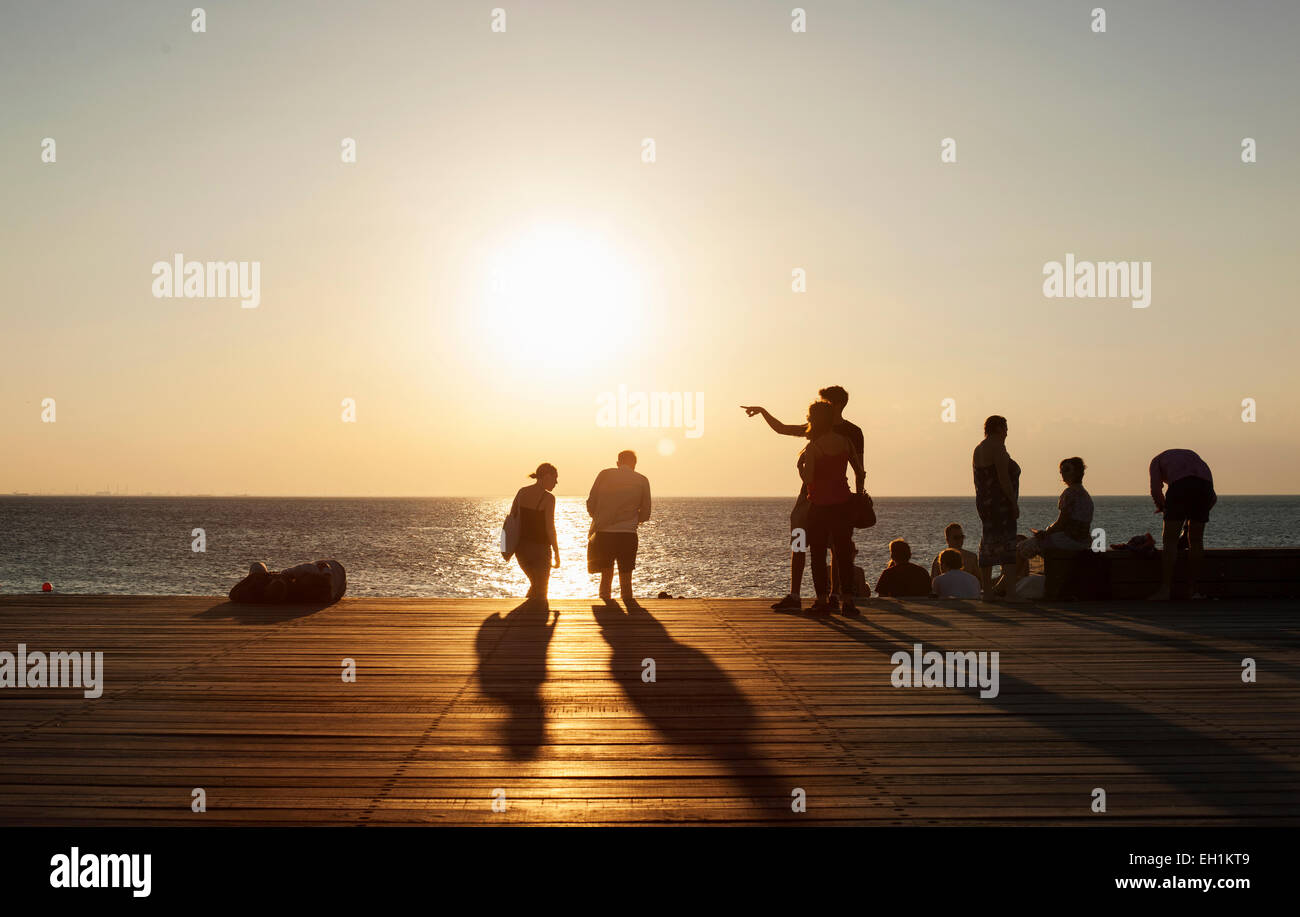 People on floorboard against sea during sunset - Stock Image