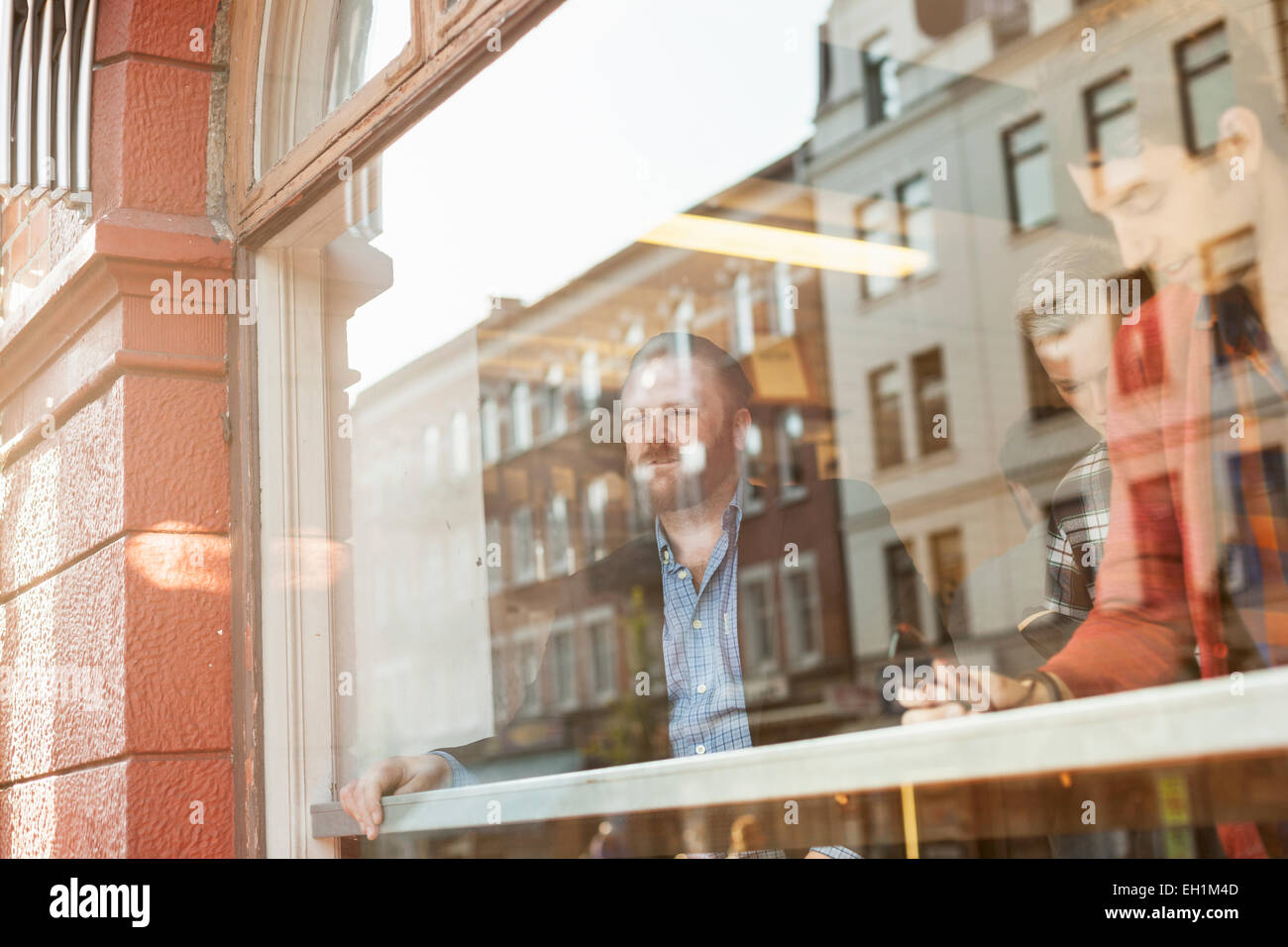 Businessmen in cafeteria seen through glass window - Stock Image