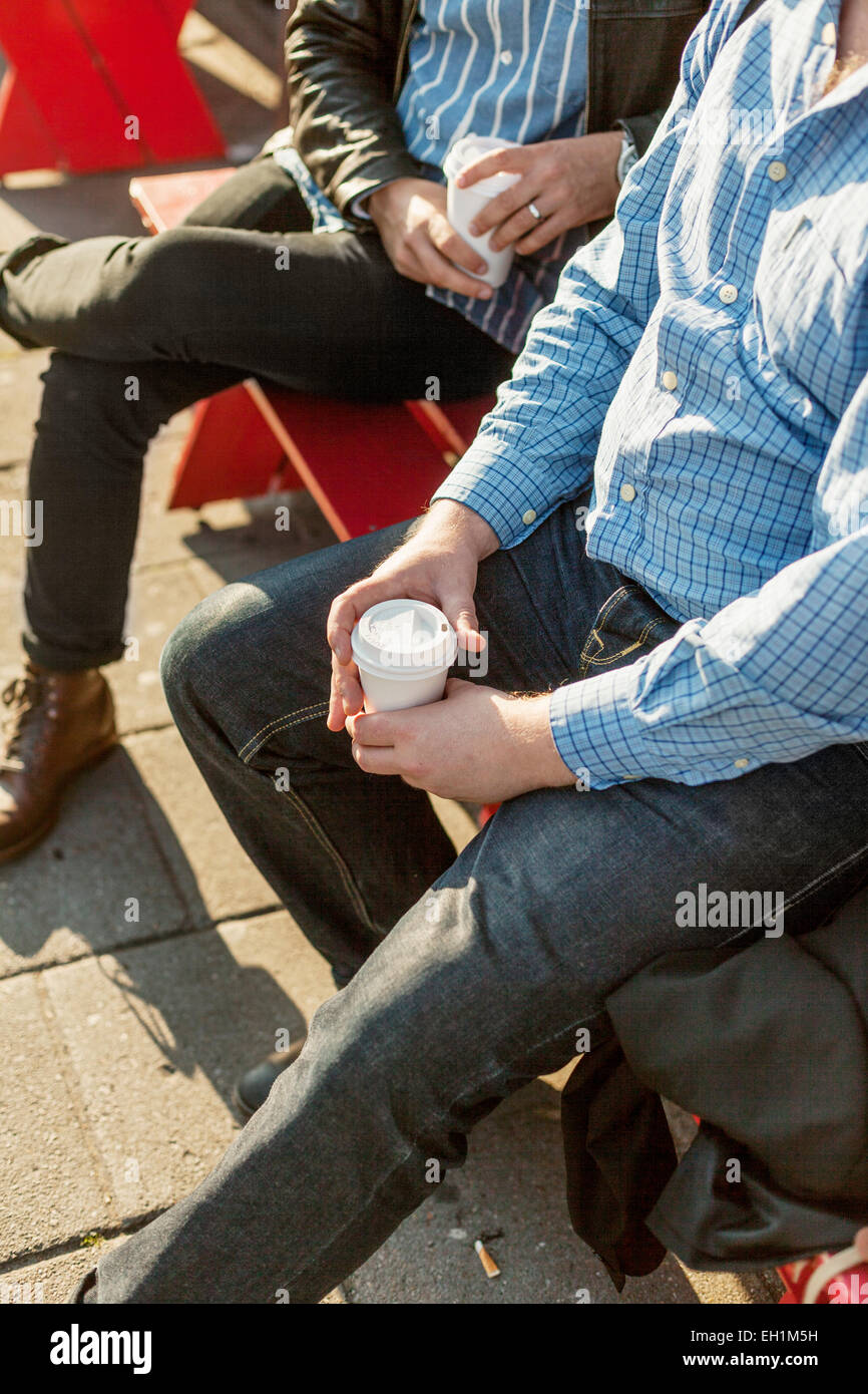 Cropped image of businessmen holding disposable cups while sitting on bench outdoors - Stock Image