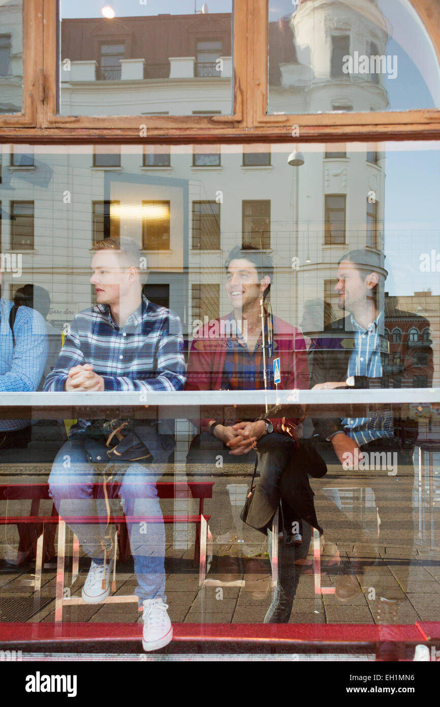 Male friends sitting in cafe seen through glass window - Stock Image