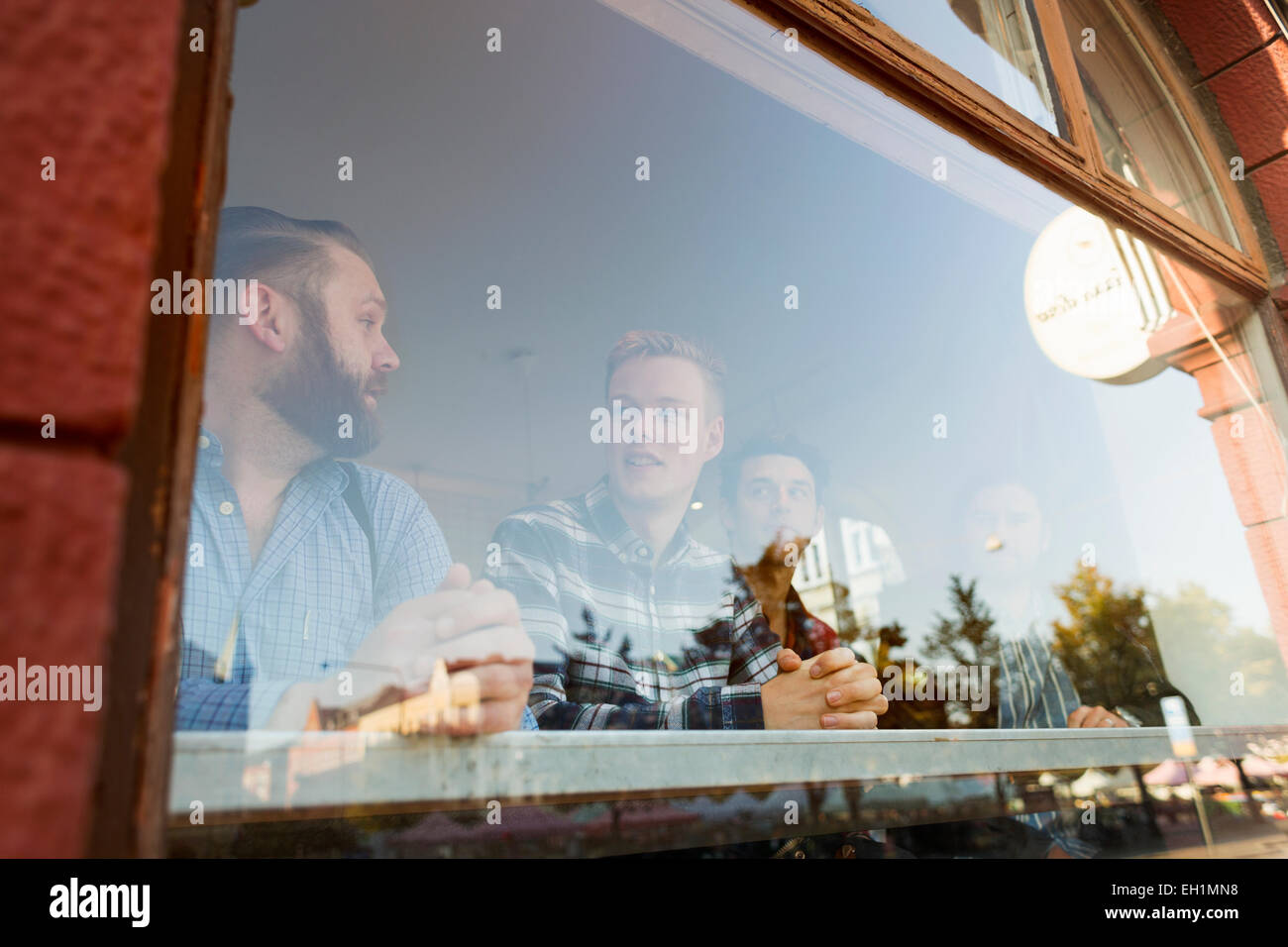 Businessmen communicating in cafe seen through glass window - Stock Image
