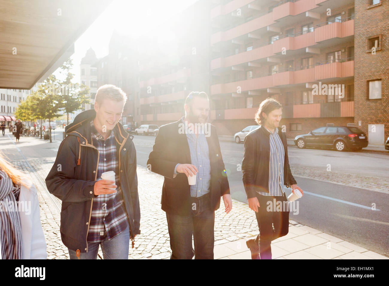 Businessmen with disposable cups walking on sidewalk in city - Stock Image