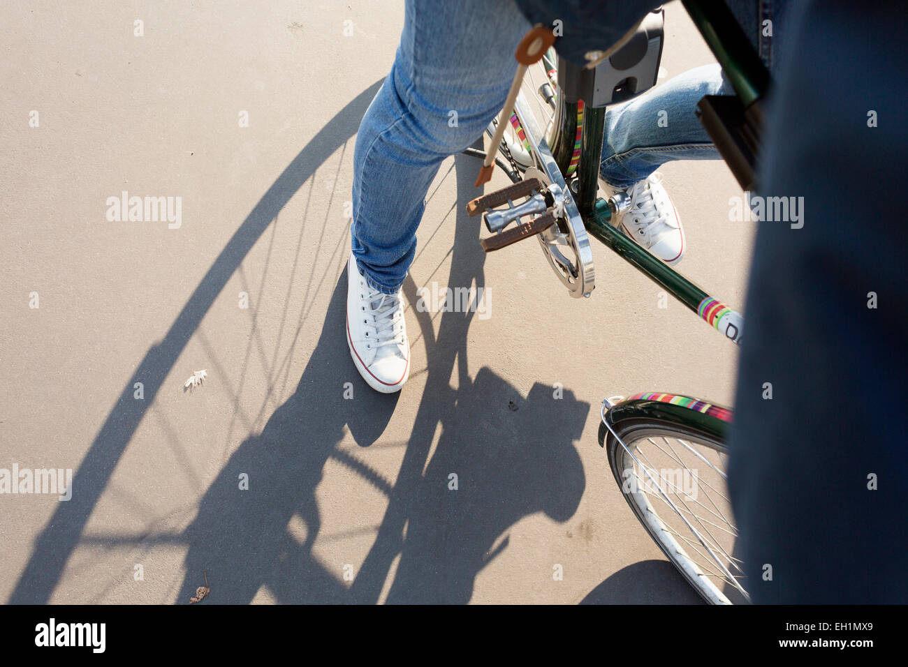 Cropped image of businessman riding bicycle on street - Stock Image