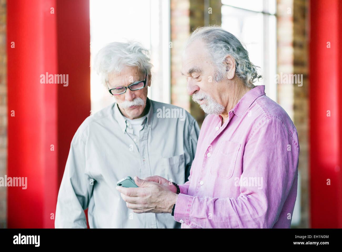 Senior men using mobile phone in gym - Stock Image