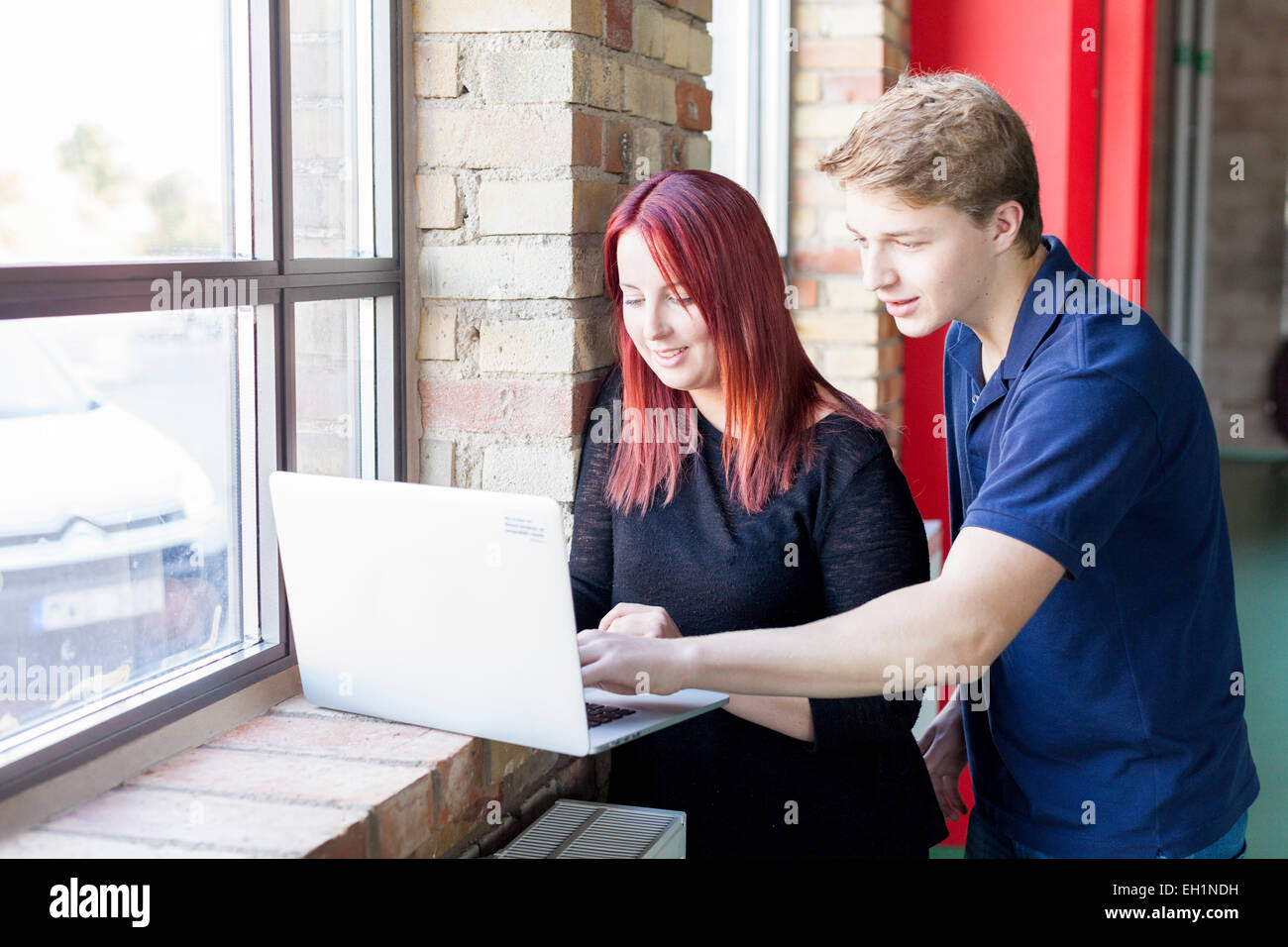Beautiful young woman using laptop in health club - Stock Image