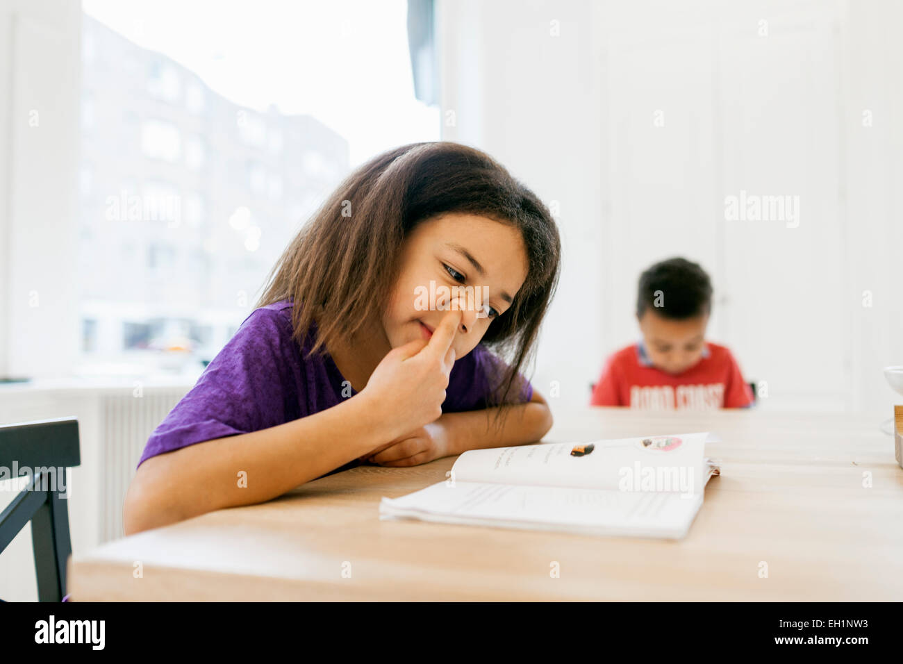 Girl picking nose while reading book with brother in background at kitchen - Stock Image