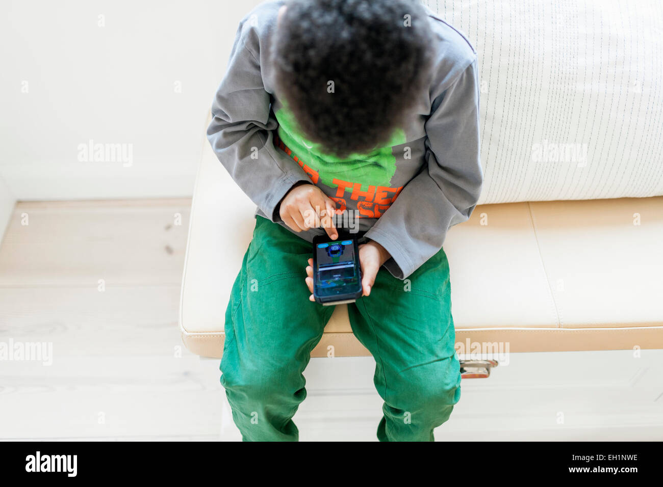 High angle view of boy playing games on smart phone at home - Stock Image